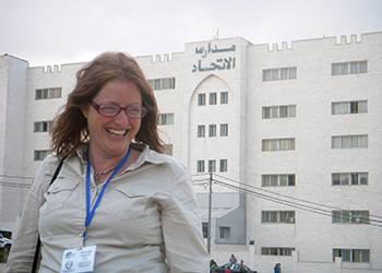 Christy Smith stands on a balcony with a white building behind her.