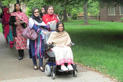 A group of women walking on a sidewalk. The group is led by disabled women including one that uses a power wheelchair and two women with visual disabilities that hold onto the back of her wheelchair.