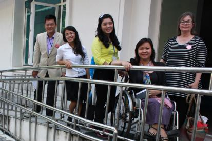 Five people stand on a ramp at the entrance of a building. One of the people is using a wheelchair.