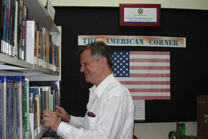 Looking at a book shelf with US flag image behind