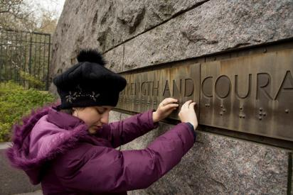 blind youth reads brailled monument strength and courage sign