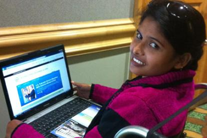 A young Bangladeshi girl is seated in her wheelchair browsing the internet on her laptop.