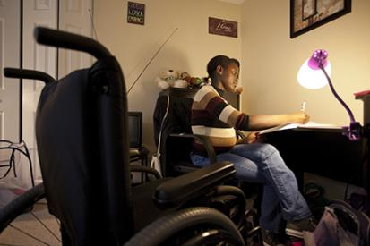 African young woman writing at desk with wheelchair empty in the foreground