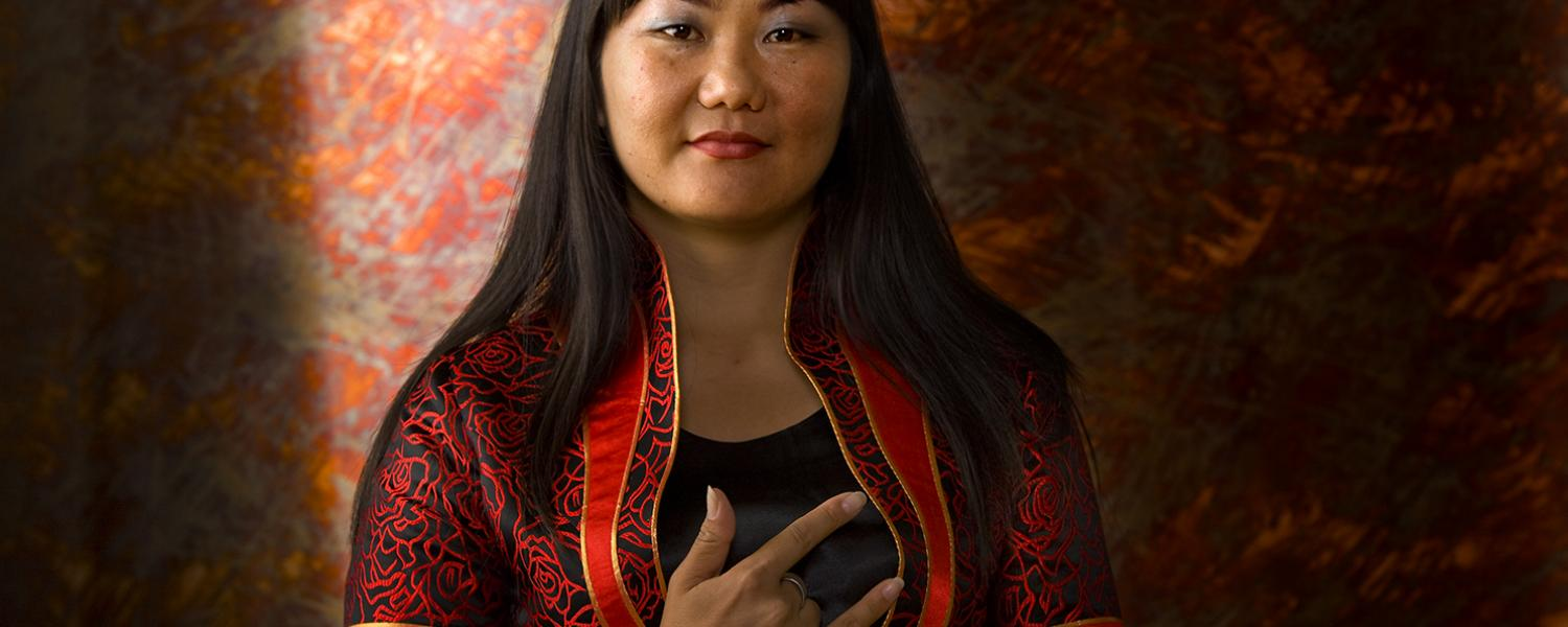 """Woman from Mongolia wearing traditional dress makes the """"I Love You"""" sign in sign language"""