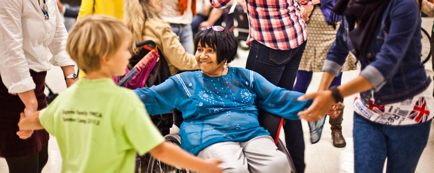 Wheelchair user, kids, adults dance in circle