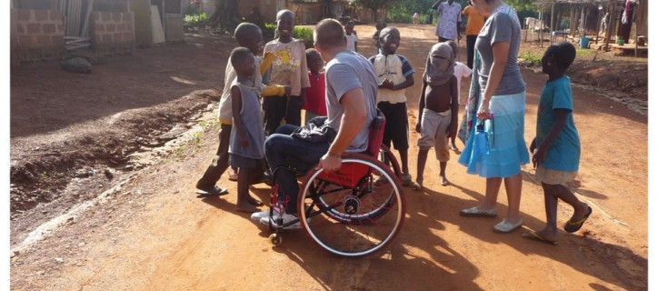 A man who is a wheelchair user in a dirt road surrounded by children