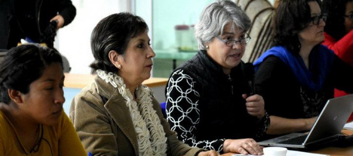 Members of RightsNow and the Mexican organization MADIJAL sit at a conference table together during a planning meeting. Susei Grimes speaks into a microphone and is surrounded by at least five more women.