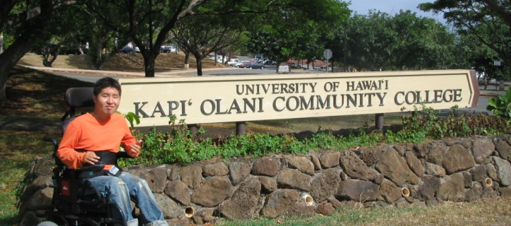 "Student, who uses a power wheelchair, poses next to ""University of Hawaii Kapi'Olania Community College"" sign outside."