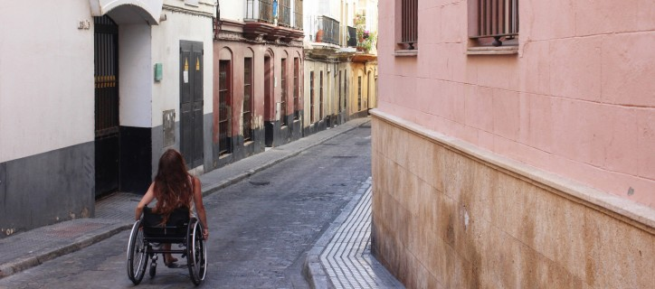 A young woman pushes herself in a manual wheelchair down a narrow street with pastel colored buildings