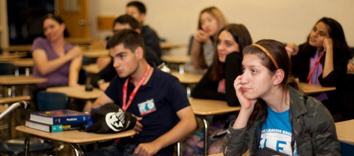 Students in a classroom listening to a presentation