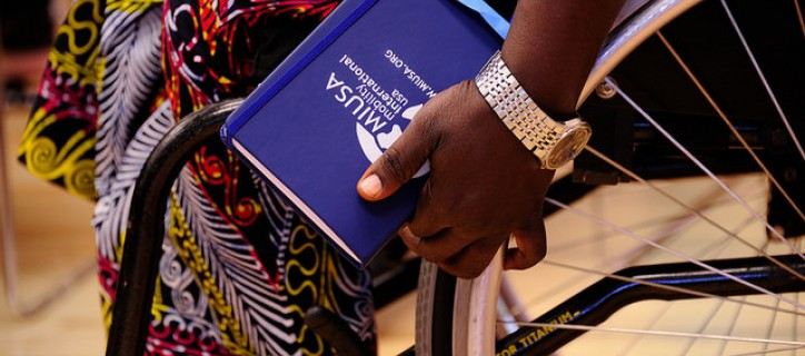 Close up of a person seated in wheelchair wearing African print skirt, with hand on wheel while also holding MIUSA logo notebook
