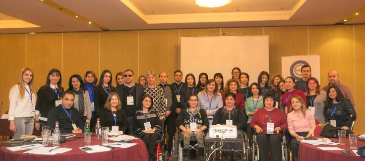 34 people with and without disabilites pose for a group photo in a conference room with the AGATE banner in the background