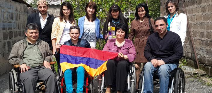 A group ten people standing and sitting in wheelchairs hold an Armenian flag.