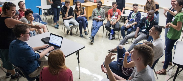 International youth with disabilities sit in a circle in a classroom smiling and talking.