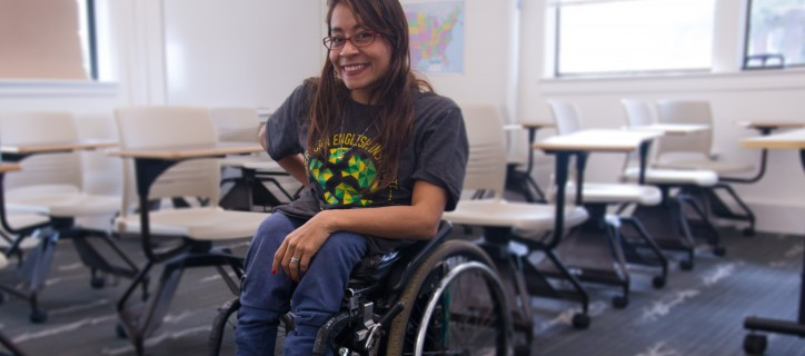 Woman, who is a wheelchair user, smiles in a classroom with desks and chairs and U.S. map on the wall.