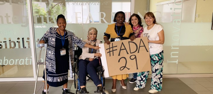 "5 WILD delegates – all of whom are women who represent different countries and diverse disabilities, ethnicities, and backgrounds – gather in a conference room holding a large hand-written sign that reads #ADA29. Some women have assistive devices such as white canes, crutches or wheelchairs, while others have non-apparent disabilities. Attire includes ""business casual,"" jeans and t-shirts, and clothing that is reflective of the women's respective regions, countries or cultures. They wear cheerful expression"
