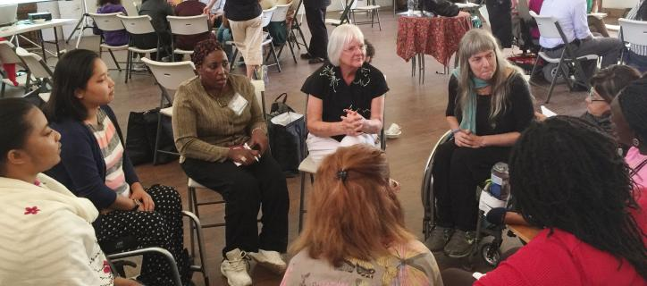 Susan speaks to a group of disabled women sitting in a circle