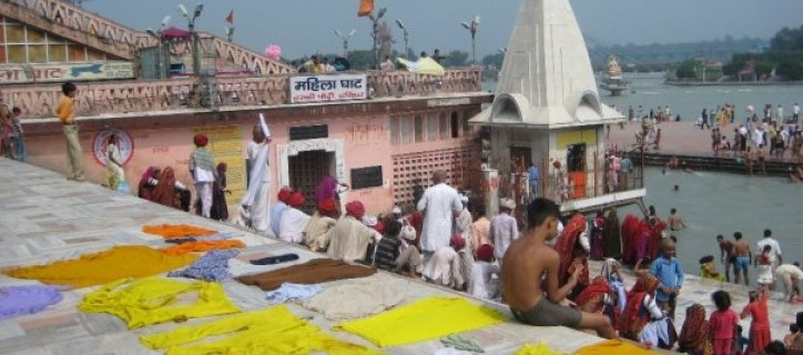 Temple in India in front of river with many people sitting on steps and going into the water. Many bright colored shirts lay to dry on top of platform.