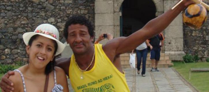Connie takes a moment to pose with a Brazilian man in front of a historic structure.