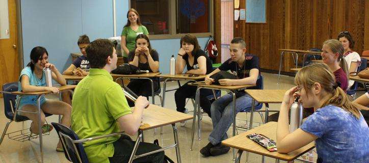 High school students sit in a semi-circle in a classroom.