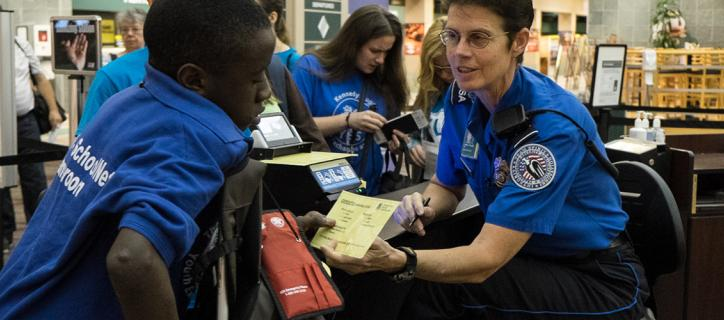 TSA checking in African student using crutches