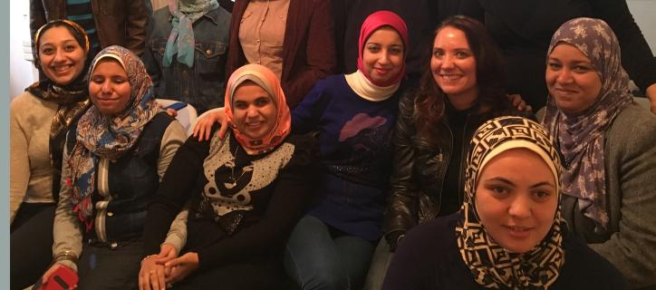 Reem sitting and smiling with students from the Association of the Visually Impaired in Alexandria, Egypt.