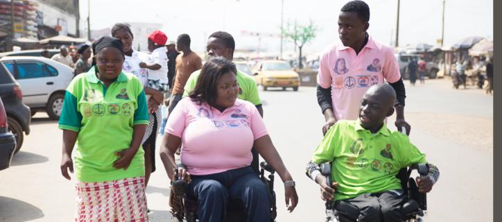 Hilda in middle of streets in Cameroon speaking with children with disabilities