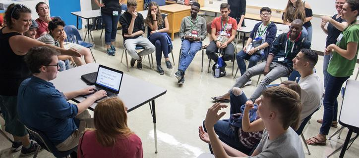 A large group of international students laughing as they sit in a circle in their chairs in a classroom. There is a man typing in front of the circle and there is a woman to the right using hand gestures to signal to one student, as he looks to her using sign language.