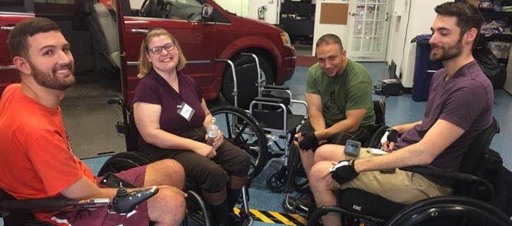 Stacy smiling in circle with group of 3 men, who are wheelchair riders, in front of an accessible van.