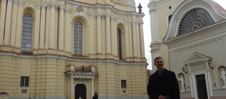 Travis Gunn in front of historical buildings in Lithuania