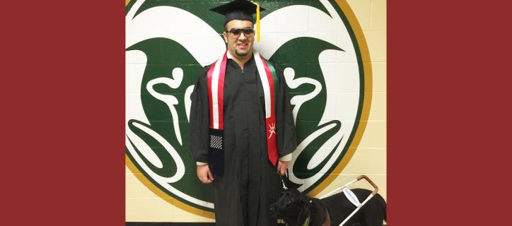 International student, who is blind, stands wearing his graduation cap and gown, with his guide dog next to him.