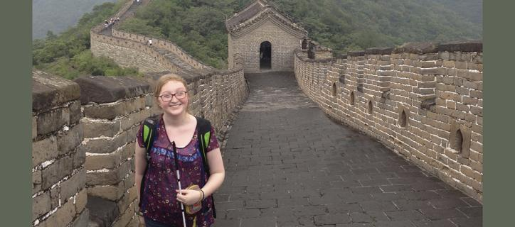 Stephanie stands at the Great Wall of China path holding her white cane.