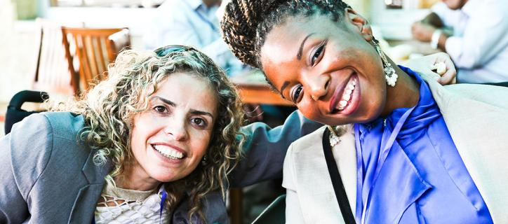 A Middle Eastern woman and African American woman wearing professional attire lean towards one another in their wheelchairs smiling.