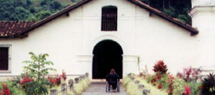 Wheelchair user on path to white stucco church in Mexico