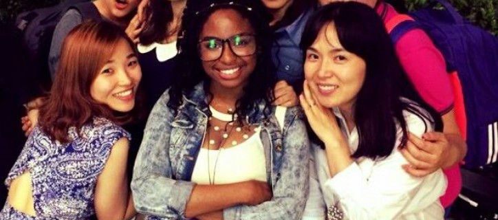 Michelle Morris (center) surrounded by six young Korean women who hug Michelle.