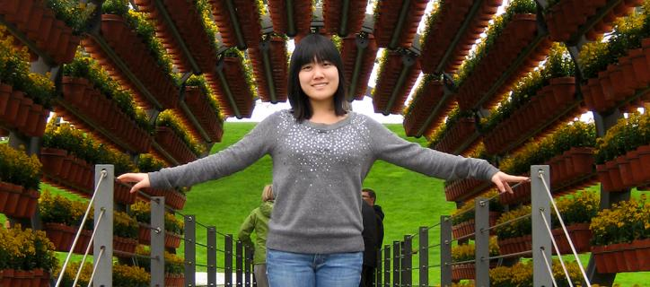 Asian-American youth stands under potted plants in Germany
