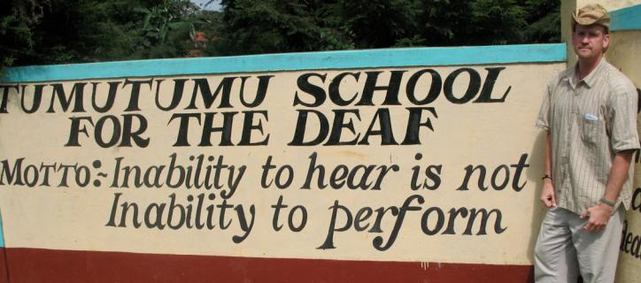 """A man stands next to a hand-painted sign that reads """"Tumutumu School for the Deaf, Motto: Inability to hear is not inability to perform"""""""