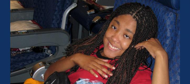Young woman seated very low in her airline seat smiles