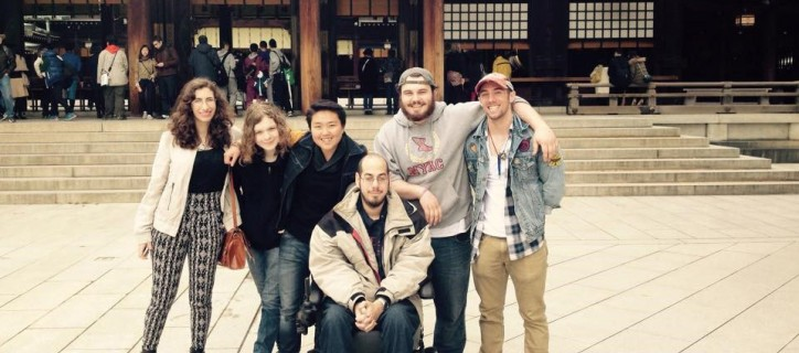 A group of men and women, including a man seated in a power wheelchair, put arms around shoulders in front of a Japanese shrine