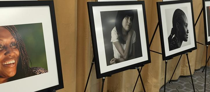 Angled view of a row of color and black and white headshots of disabled women displayed on easels