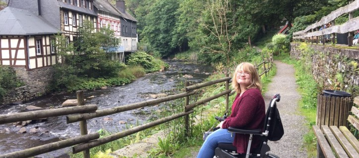 Brooklyn, seated in an electric wheelchair on a gravel path, faces a narrow river and German house