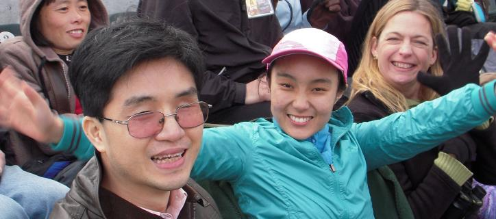 International students sitting and smiling on bleachers at sports game.