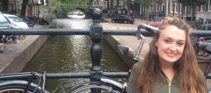 young woman sits on the bridge of a canal, with bicycle and canal visible behind her