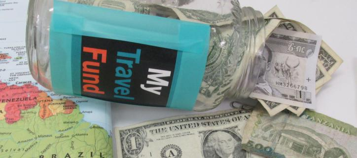 """Money spills out of a jar labeled """"My travel fund"""""""