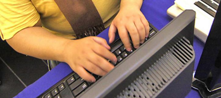 Hands typing at a computer keyboard