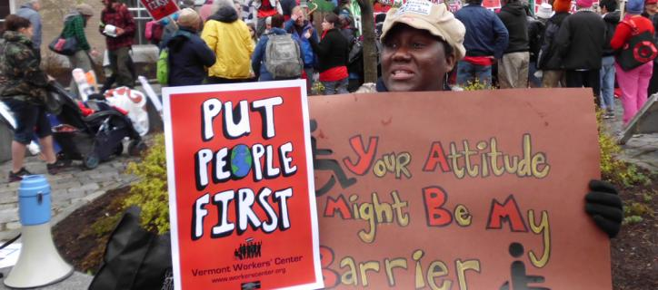 Protest signs say Put People First. Your Attitude May be My Barrier
