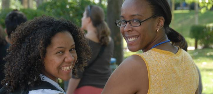 Two young women of color have their arms clasped and are smiling brightly for the photo.