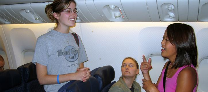 Two Deaf women communicate with each other in sign language on an airplane.