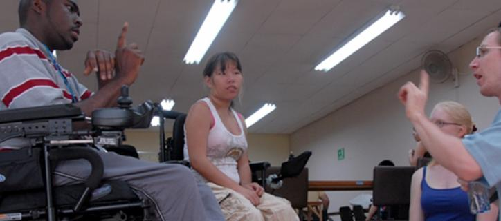 In a classroom setting, a Deaf man leads a group of other individuals with different types of disabilities in learning different signs.