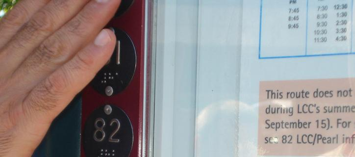 Hand of someone reading braille on the edge of a public bus posted schedule
